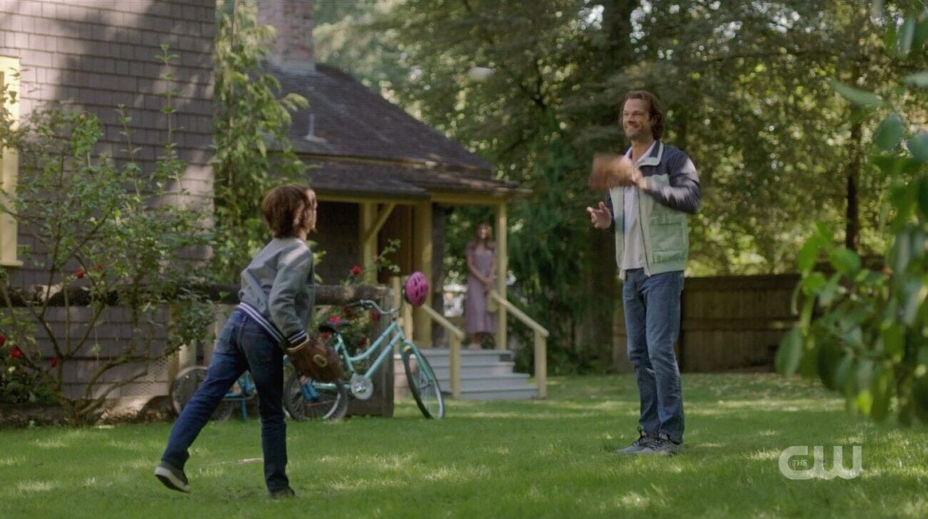 Sam plays catch with his son Dean while blurry blonde woman looks on from the porch in the Supernatural finale