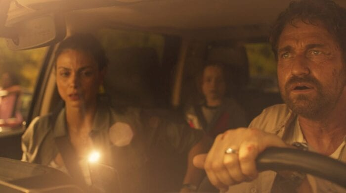 John Garrity is perched behind the wheel of his car, leaning over the steering wheel at the sky ahead. Allison sits in the passenger seat and Nathan behind her in the back seat, a bright light is reflecting on the winshield.