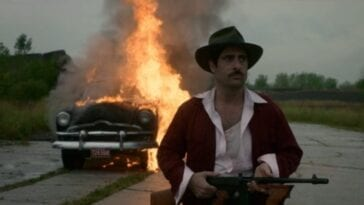 A man in a hat with a gun walks away from a burning car