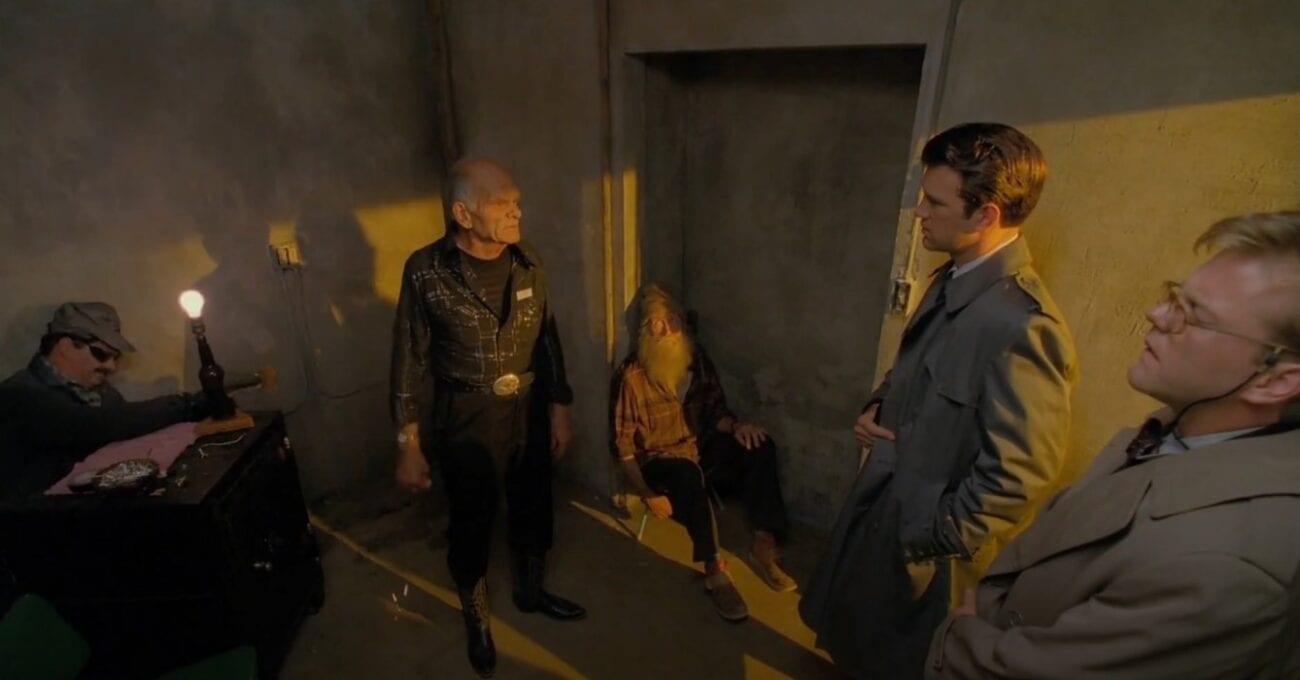 FBI agents Desmond and Stanley, in grey trench coats, question an old man dressed in black, while a man with a beard sits on the floor and another man works on a faulty lamp.