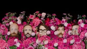 The faces of IDLES peep up from flowers painted in the style of Van Gogh