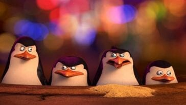 Penguins of Madagascar screenshot featuring, from left to right, Kowalski, Skipper, Rico, and Private. All bare serious expressions, save for Rico, who looks a bit disgusted, just having coughed up a pile of sand. They are peeking out of a manhole cover in front of many colorful lights, blurred to the point of being hardly distinguishable from anything else sparkly.