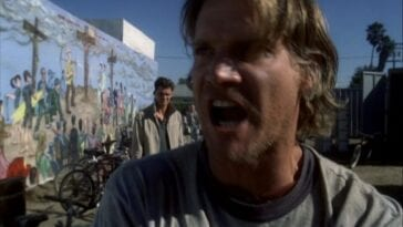 Butchie rants angrily toward the camera as John stands behind him with a mural of three crosses on a hilltop and surfers running toward them on the wall in the background