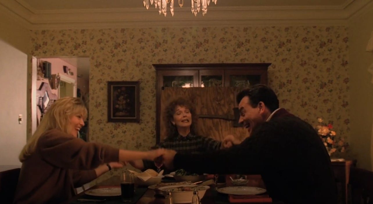 The Palmer family hold hands and laugh around the dinner table. An axe mounted on a plank of plywood is resting against the cabinet in the background.
