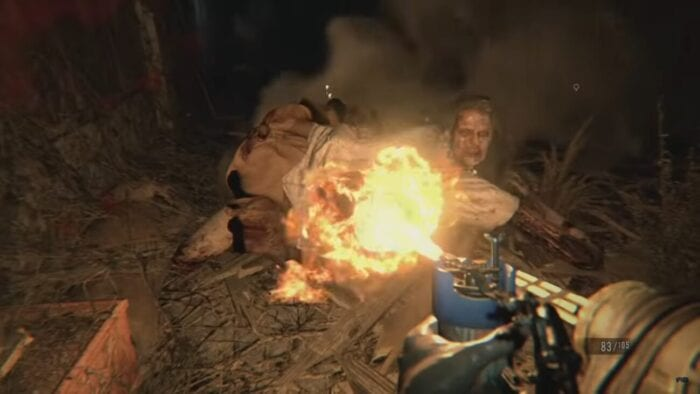 A flamethrower is used against a large limbed woman who appears crawling, looking like she has just swatted the flame