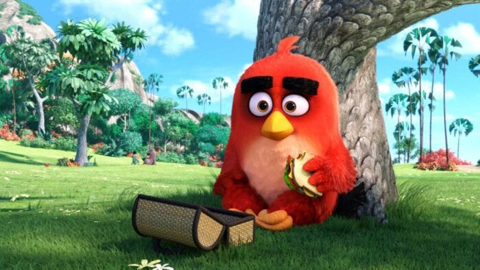 Angry Birds lead Red (a rather oval-shaped red bird with pinkish coloring on his chest/stomach, large rectangular black eyebrows, a yellow beak, fiery brown eyes, and orange feet) eating a sandwich under a tree. He's sitting on top of bright green grass, his wicker lunchbox in front of him. It's a bright and sunny day; a couple other birds can be seen sitting together in the background.