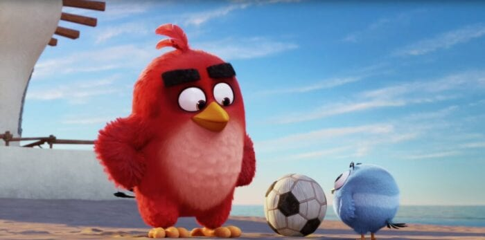 Red standing outside his house (barely visible as it's off to the side) staring down at a tiny, round blue bird who is playing with a soccer ball. Red's hands are on his hips and he looks smug, as he is about to punt the small fella into the sea.