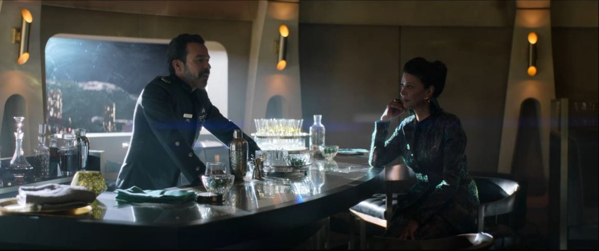 Delgado stands behind a bar talking to Avasarala on the other side