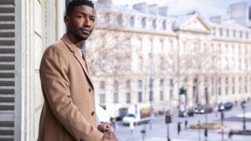Elijah, a man with fuzzy black hair and thin facial hair, standing on a hotel balcony in Paris. He's wearing a light brown coat, hands resting on the balcony rails as he looks in the general direction of the camera. He looks happy.