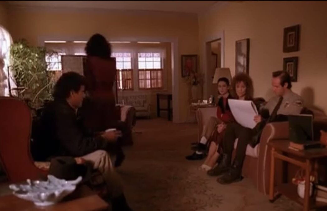 A wide shot of the Palmer living room. The sheriff sits across from the couch containing Donna, Sarah and Andy.