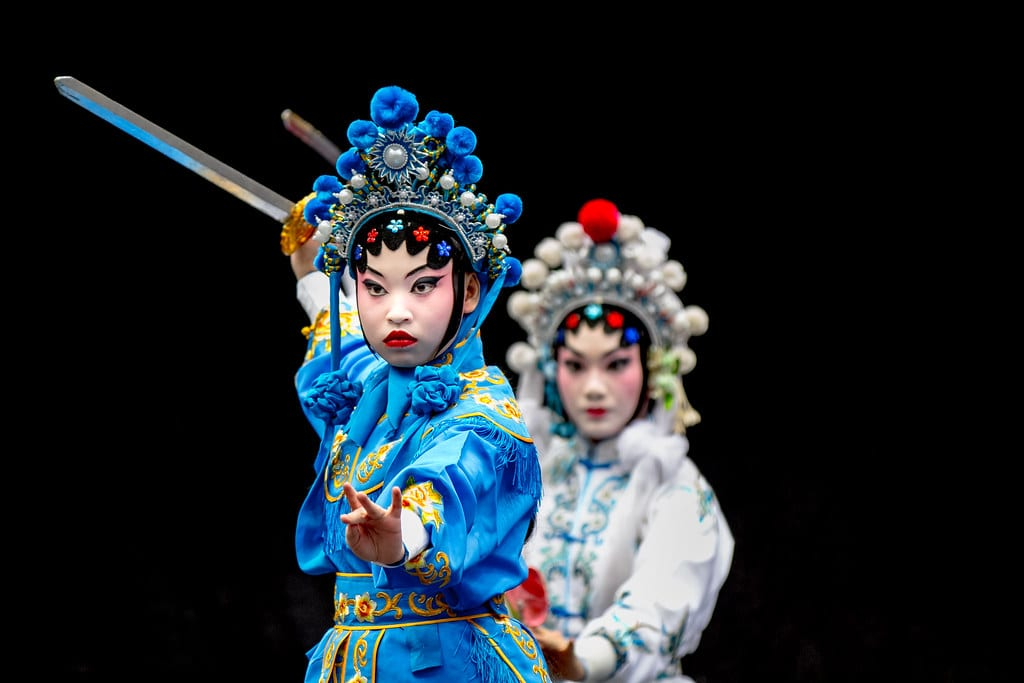 Two actors in traditional Chinese Opera costumes stand one in front of the other with their swords raised.