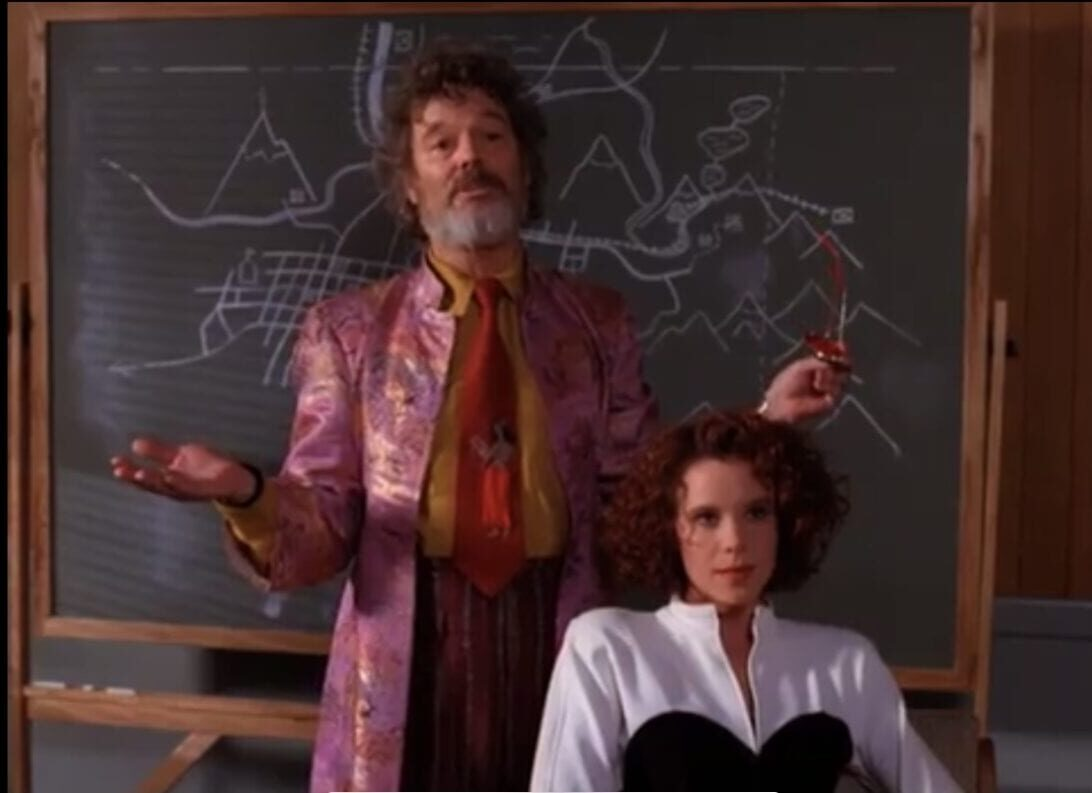 Jacoby, in purple coat and red tie, stands behind Lana Milford in twin peaks episode 21