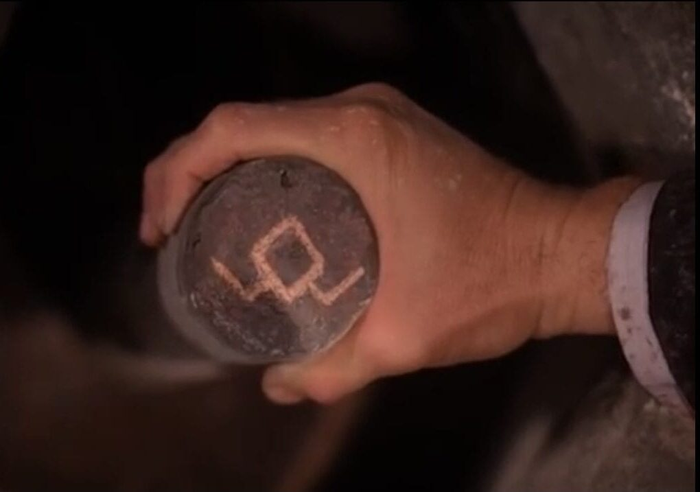 The owl symbol, turned upside down, while Earle's hand turns the post more.