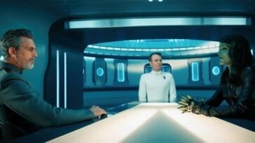 Admiral Vance (Oded Fehr), Eli (Brendan Baiser), and Osyraa (Janet Kidder) sit around a white conference table with blue monitors in the background