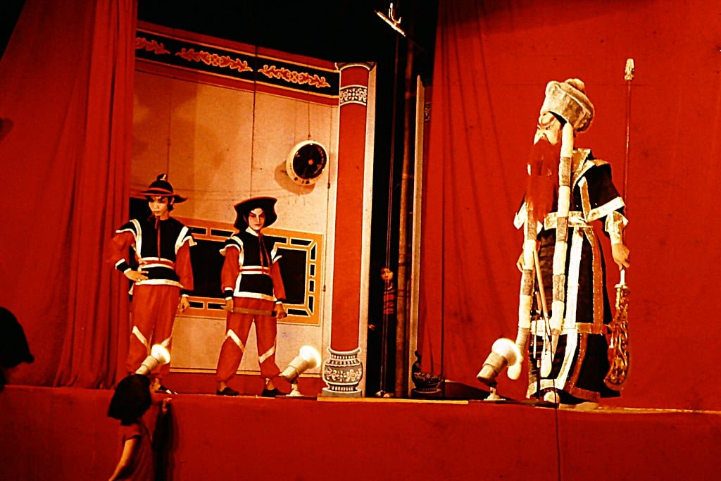 Three actors stand on stage in a Chinese Opera. The background and floor are red and the two off to the left are dressed as guards while the actor to the right is dressed in full ceremonial robes of the Emperor