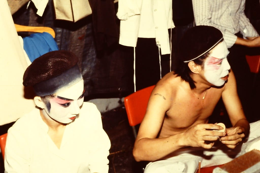 Backstage at a Chinese theatre, two performers are seen putting on traditional Chinese Opera make-up.