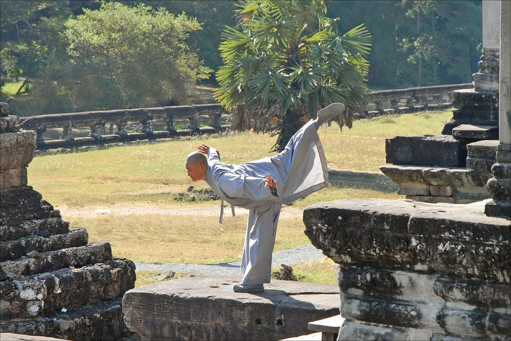 A MArtial Artist stands on one leg, with his other stretched out behind him, on a tone wall of Angkor Wat