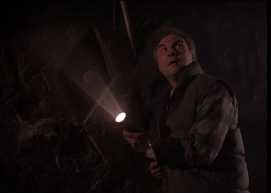 Windom, looking up in wonder, in a dark cave while holding a flashlight.