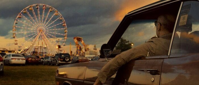 Charlie watches a carnival while in his car.
