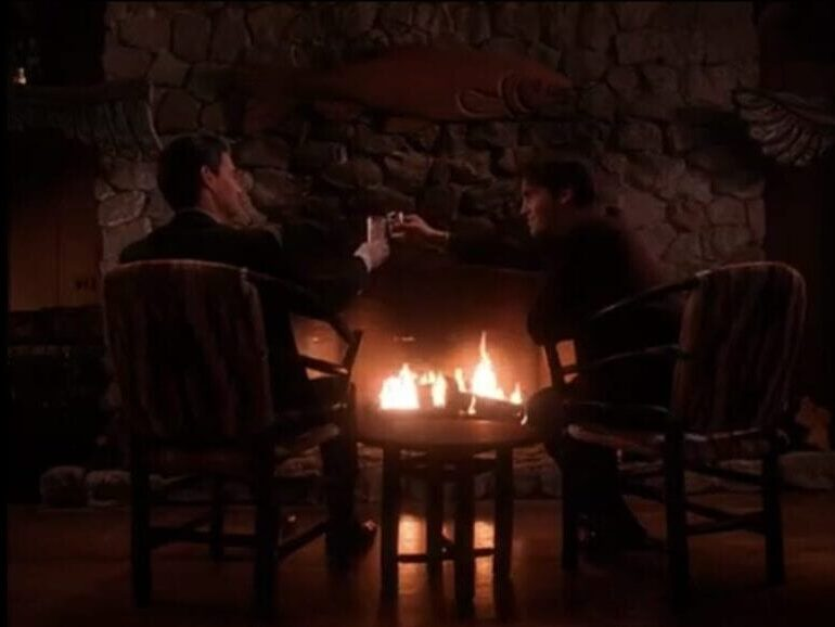 Special Agent Dale Cooper and John Justice Wheeler toast by a fire at the Great Northern