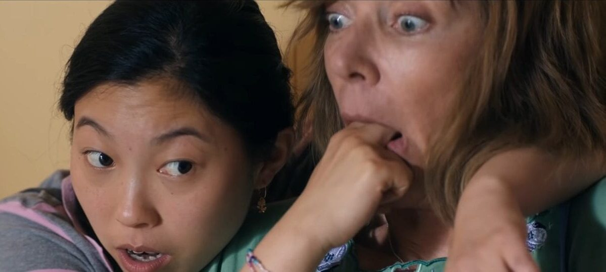 Awkwafina puts her fingers down Alison Janneys mouth while wrapping her other arm around her shoulder