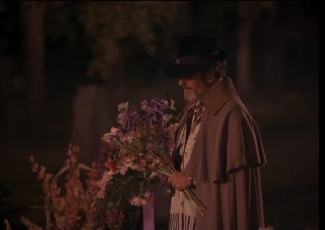doctor jacoby wears a showy trench coat and holds flowers before a grave.