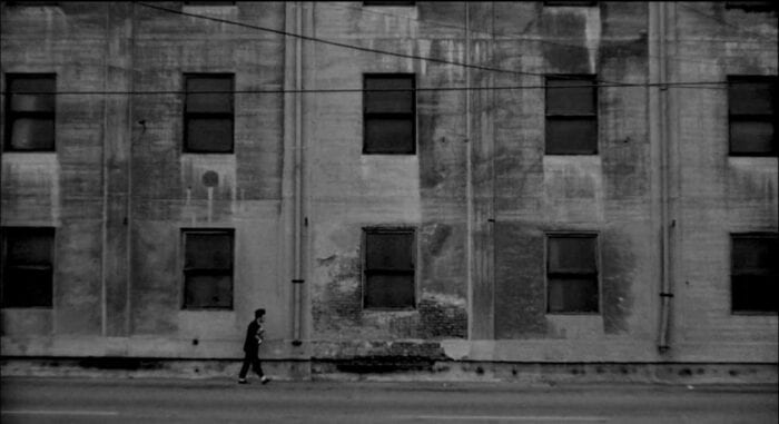 Henry (Jack Nance) walks by himself past a dilapidated factory.