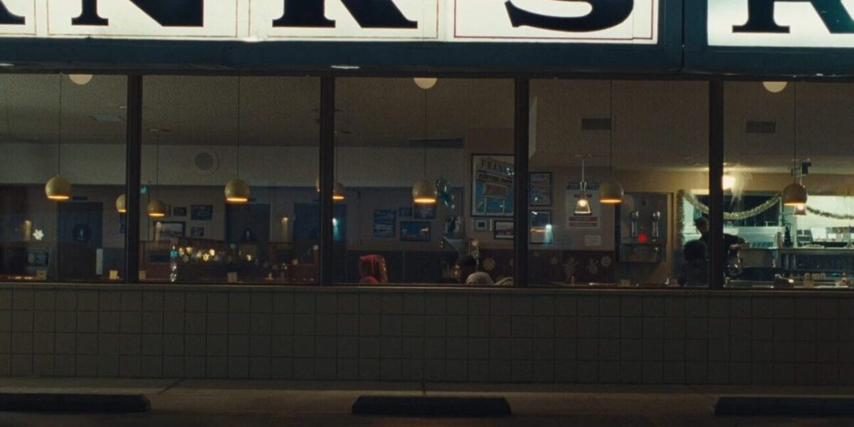 an outside looking in view of Rue and Ali sit at a booth inside a diner