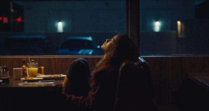 Rue leans back in a booth next to large windows at the diner and looks toward the ceiling