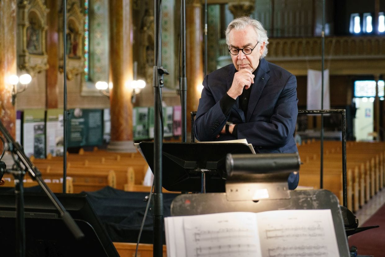 Howard Shore stands at a podium overlooking sheet music