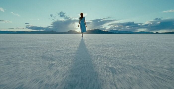 A woman walks on a salt flat on a partly cloudy day.