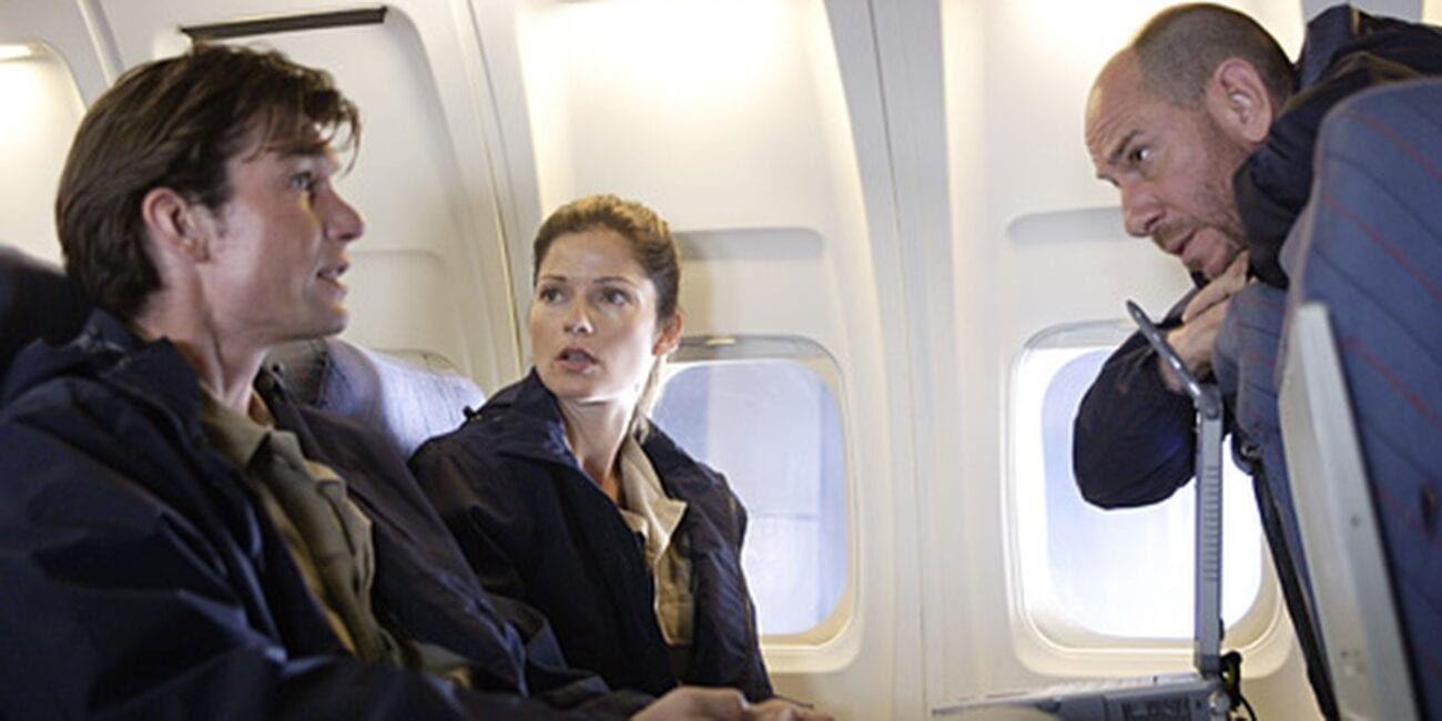 Woody and Jordan sitting next to each other on a plane with Garret looking at them from over the seat in Crossing Jordan