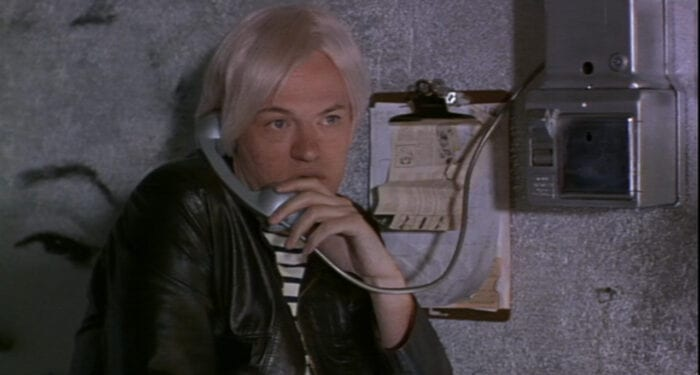 Andy Warhol (Jared Harris) uses a phone attached to the wall