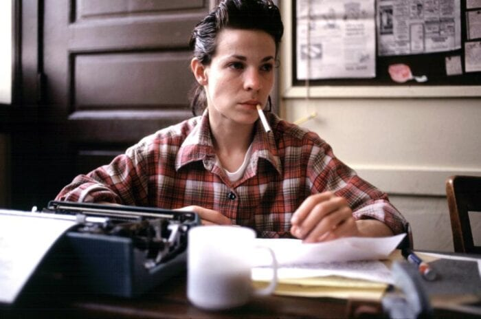 Valerie Solanas (Lili Taylor) sits at a desk covered in papers, a typewriter to her right. She is smoking a cigarette
