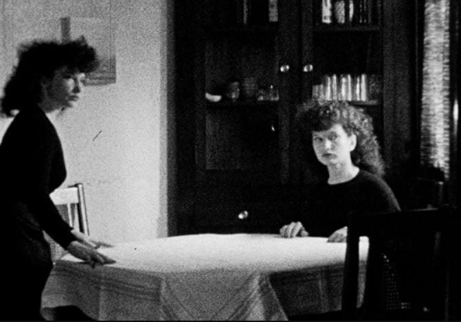 Two Maya Derens at a dinner table. One is standing as if about to sit down, the other is seated. They are both looking off-camera.