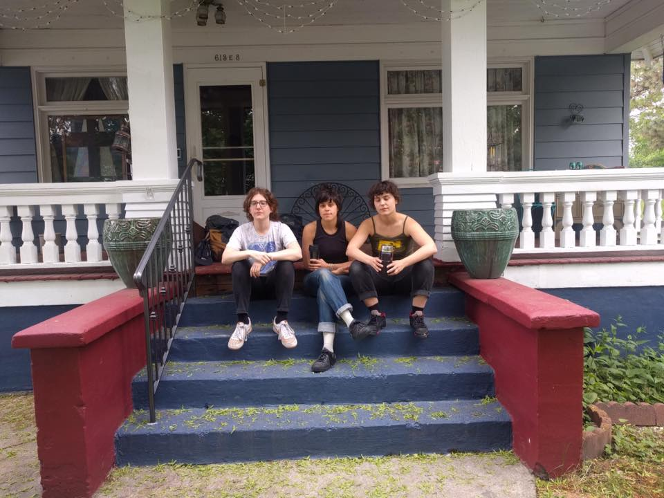 The three female members of Palberta sitting on the steps outside a house looking at the camera