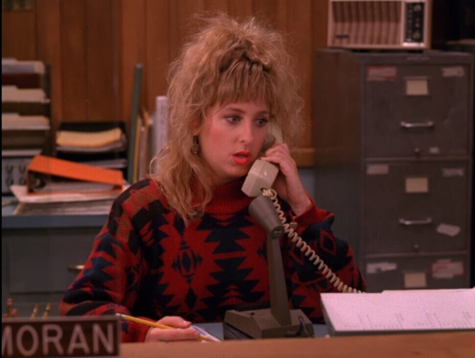 Lucy answers the phone at the reception desk, looking confused.