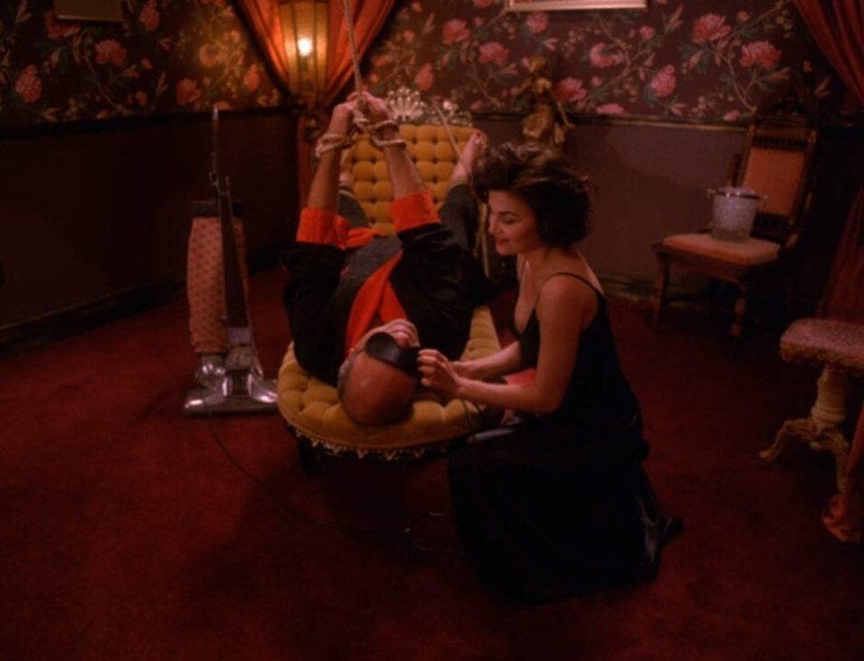 Audrey kneels before an upside-down, blindfolded Battis, teasing him