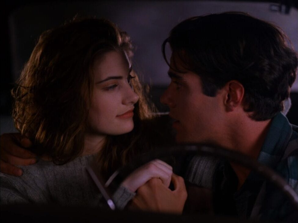 Shelly and Bobby sit close together behind the wheel of a car, staring into each other's eyes