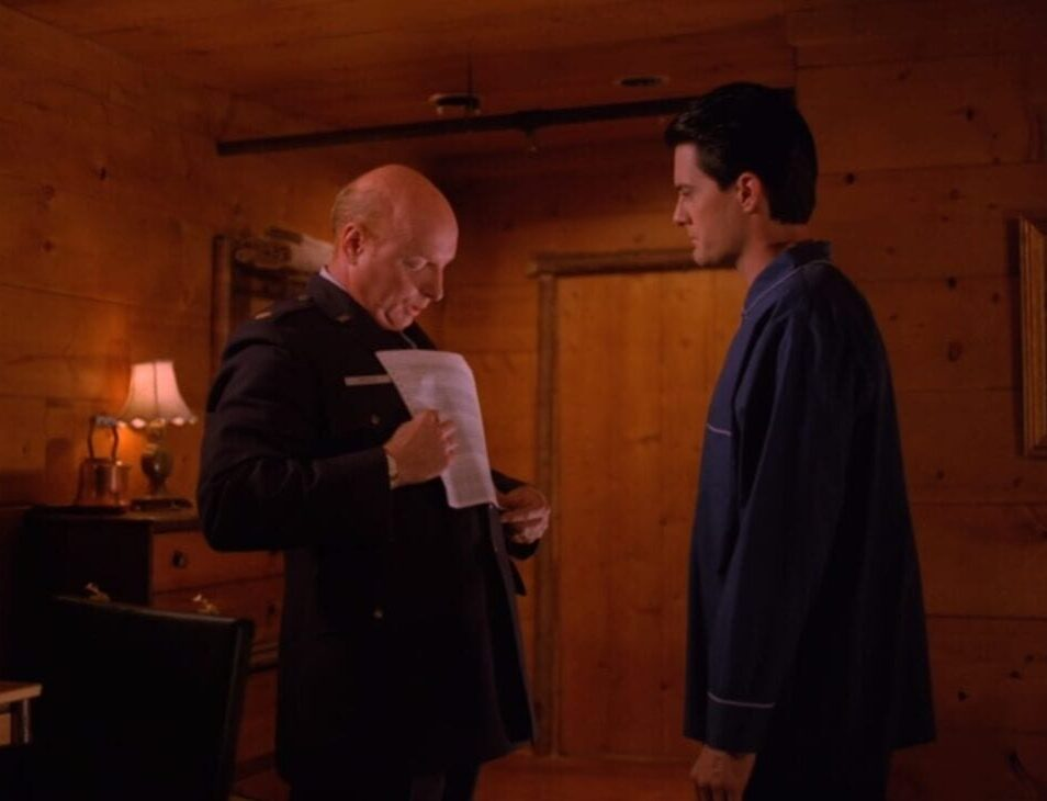 Major Briggs stands before a pajama-clad Cooper in the latter's hotel room, a piece of paper in his hand