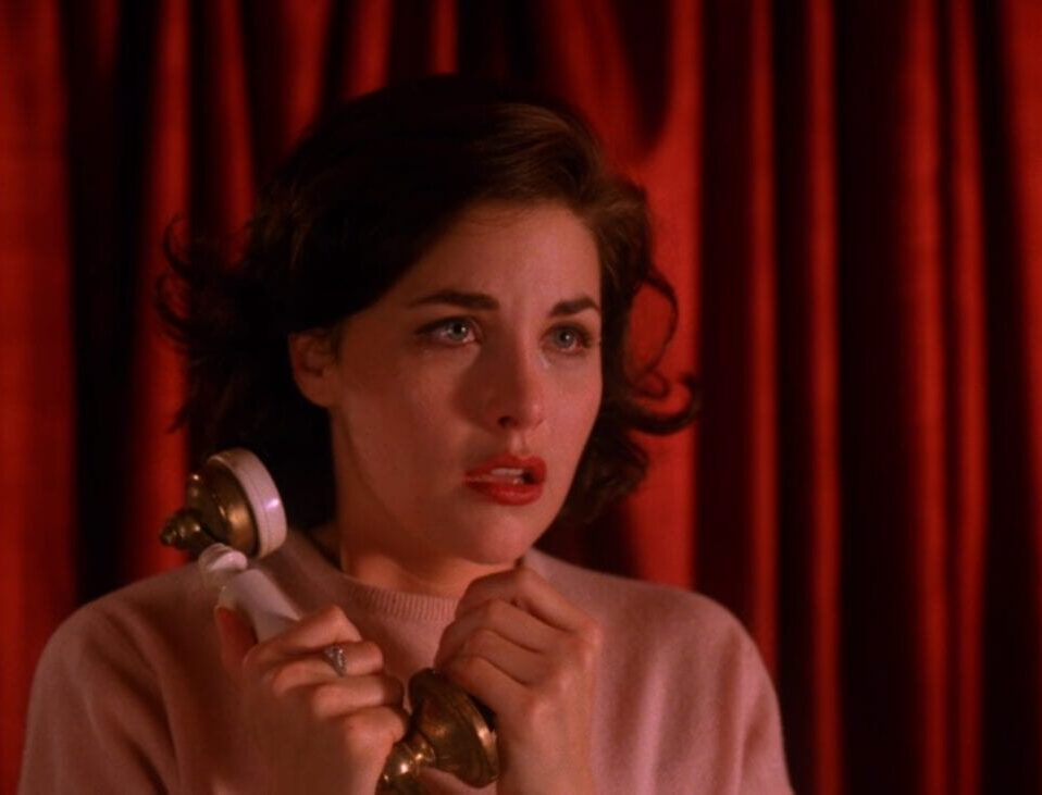 Audrey looks frightened offscreen, clutching a telephone by her face