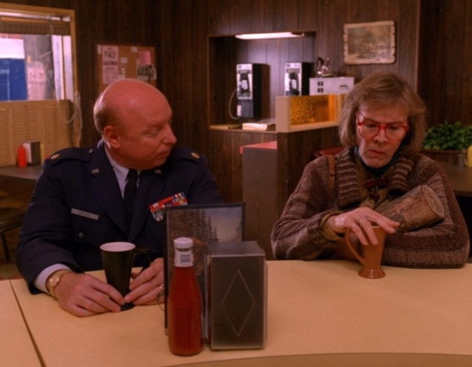 Major Briggs sits at the Double R counter next to the Log Lady, Margaret, holding her log