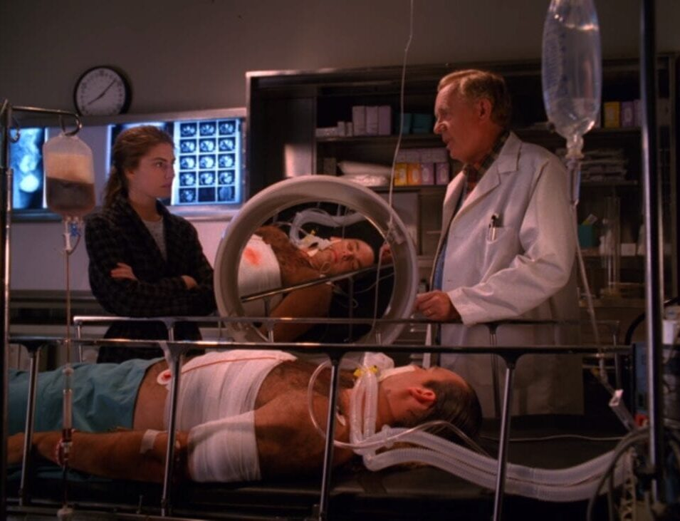Shelly and Doc Hayward stand over Leo's hospital bed, a magnifying glass reflected Leo's face.