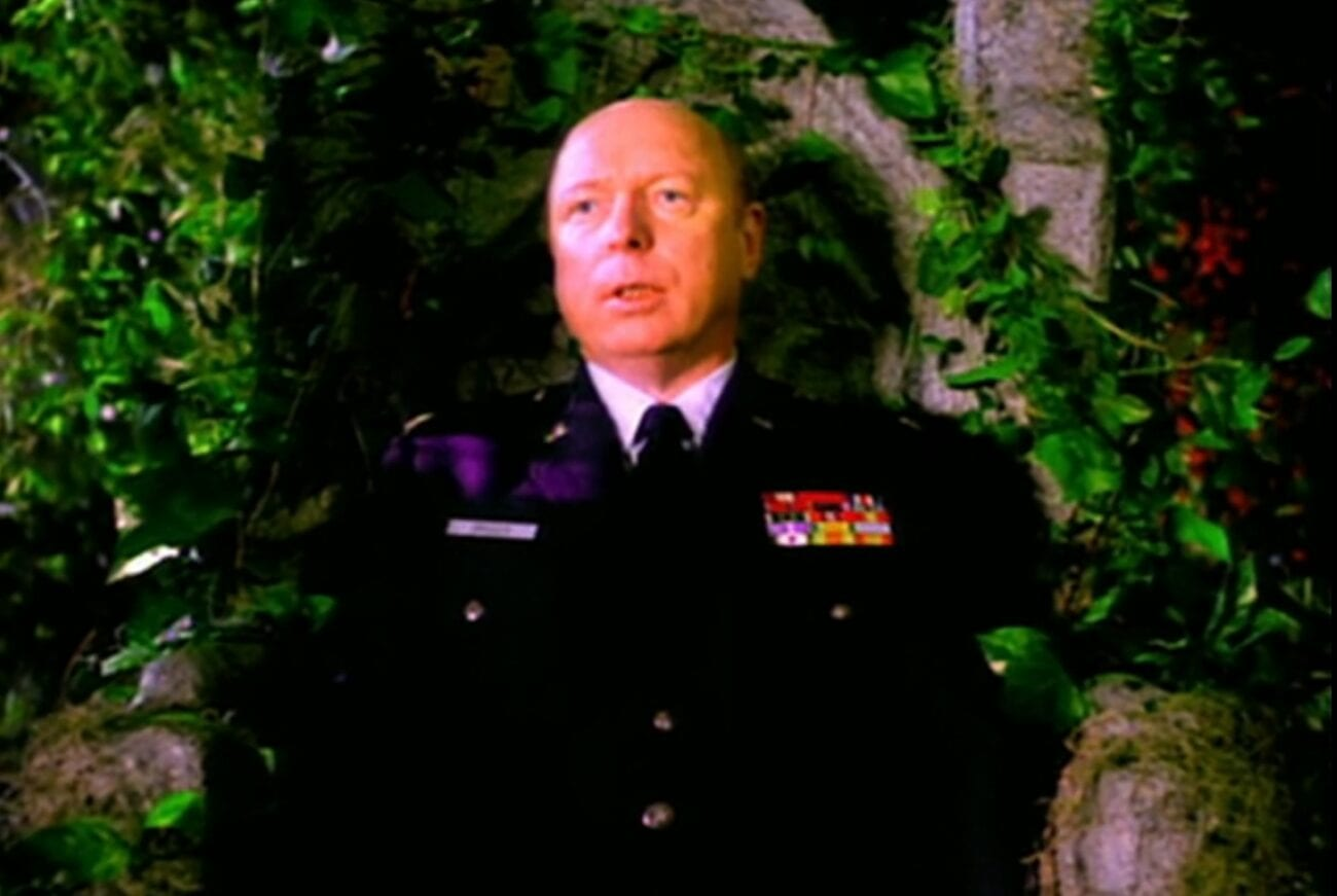 Major Garland Briggs in uniform and staring out into the distance while sitting on a stone throne covered in green ivy.