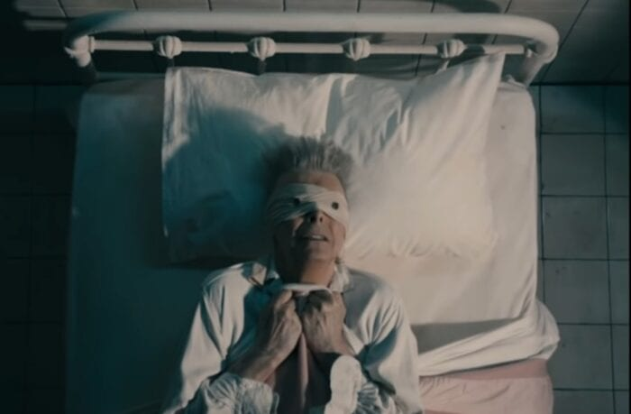 "David Bowie in a bed clutching the covers and wearing a button-eyed blindfold from the video for ""Lazarus."""