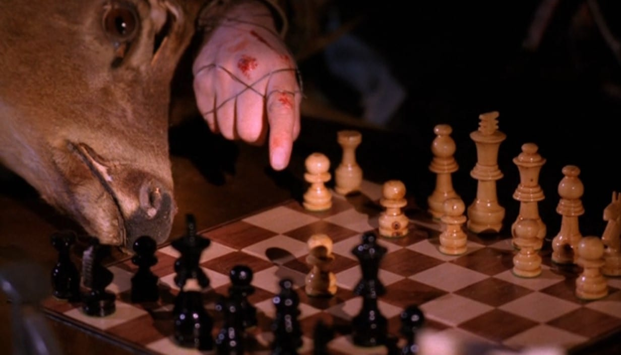 A hand studded with scars points to a move on a chessboard