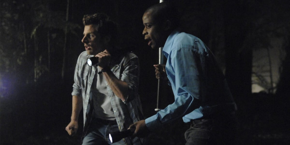 Shawn and Gus in the dark with flashlights looking frightened in Psych 2000s TV