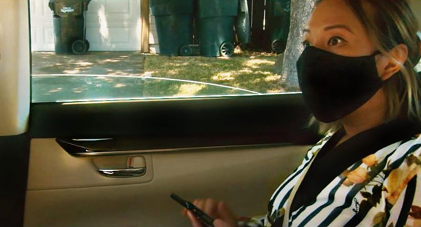 Arlene Barshinger wearing a black mask rides in a car driving through Los Angeles