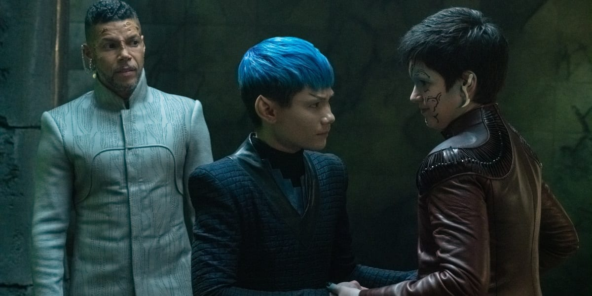 Gray (Ian Alexander) as a Vulcan and Adira (Blu Del Barrio) hold each other as Culber (Wilson Cruz) looks on in the holo-program