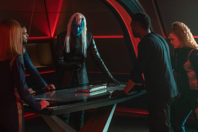 The Bridge crew and Ryn stand around a table in the red lit Ready Room